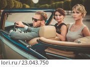 Купить «Wealthy friends in a classic convertible», фото № 23043750, снято 11 августа 2015 г. (c) Andrejs Pidjass / Фотобанк Лори