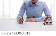Купить «woman with house model and pen signing contract», видеоролик № 23053018, снято 14 мая 2016 г. (c) Syda Productions / Фотобанк Лори