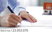 Купить «woman with house model and pen signing contract», видеоролик № 23053070, снято 14 мая 2016 г. (c) Syda Productions / Фотобанк Лори