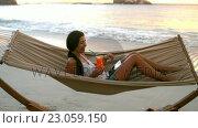 Купить «Woman using digital tablet and having mocktail on a hammock», видеоролик № 23059150, снято 18 июля 2019 г. (c) Wavebreak Media / Фотобанк Лори