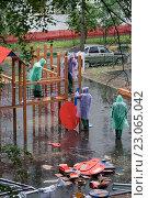 Купить «Рабочие в разноцветных плащах под дождем собирают оборудование детской площадки», фото № 23065042, снято 7 июня 2016 г. (c) Наталья Николаева / Фотобанк Лори
