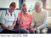 Купить «Doctor writing medical report of senior couple», фото № 23072166, снято 22 марта 2016 г. (c) Wavebreak Media / Фотобанк Лори