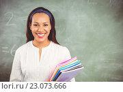 Купить «Portrait of smiling school teacher holding books in classroom», фото № 23073666, снято 6 марта 2016 г. (c) Wavebreak Media / Фотобанк Лори