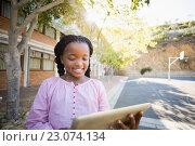 Купить «Happy school girl using digital tablet in campus», фото № 23074134, снято 6 марта 2016 г. (c) Wavebreak Media / Фотобанк Лори