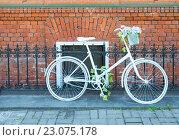 Белый велосипед у кованной ограды на фоне кирпичной стены. Стоковое фото, фотограф Илья Беспальчиков / Фотобанк Лори