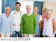 Купить «Nurse and seniors standing together», фото № 23075654, снято 2 марта 2016 г. (c) Wavebreak Media / Фотобанк Лори