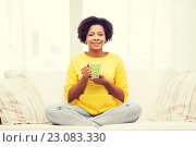 Купить «happy african american woman drinking from tea cup», фото № 23083330, снято 4 июня 2015 г. (c) Syda Productions / Фотобанк Лори