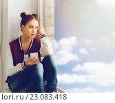 Купить «teenage girl sitting on windowsill with smartphone», фото № 23083418, снято 19 декабря 2015 г. (c) Syda Productions / Фотобанк Лори