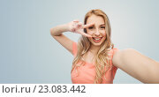 Купить «smiling woman taking selfie and showing peace sign», фото № 23083442, снято 30 апреля 2016 г. (c) Syda Productions / Фотобанк Лори