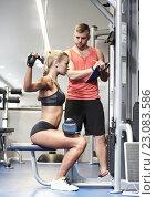 Купить «man and woman flexing muscles on gym machine», фото № 23083586, снято 19 апреля 2015 г. (c) Syda Productions / Фотобанк Лори