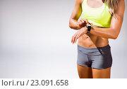 Купить «Composite image of sporty woman looking her watch», фото № 23091658, снято 16 декабря 2018 г. (c) Wavebreak Media / Фотобанк Лори