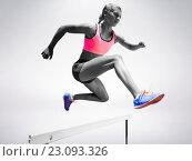 Купить «Sporty woman jumping a hurdle», фото № 23093326, снято 17 октября 2018 г. (c) Wavebreak Media / Фотобанк Лори