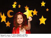 Купить «Девочка в красном плаще с капюшоном стоит на черном фоне и держит в руке звезду», фото № 23093670, снято 2 апреля 2016 г. (c) Сергей Новиков / Фотобанк Лори