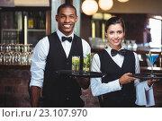 Купить «Waiter and waitress holding a serving tray with glass of cocktail», фото № 23107970, снято 15 марта 2016 г. (c) Wavebreak Media / Фотобанк Лори