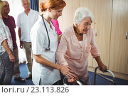 Nurse helping a retired woman to walk. Стоковое фото, агентство Wavebreak Media / Фотобанк Лори