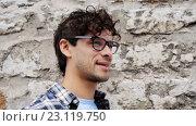 Купить «happy smiling man in eyeglasses over street wall 20», видеоролик № 23119750, снято 16 июня 2016 г. (c) Syda Productions / Фотобанк Лори