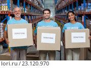 Купить «Happy volunteers are holding donations boxes and looking the camera», фото № 23120970, снято 23 марта 2016 г. (c) Wavebreak Media / Фотобанк Лори
