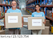 Купить «Happy volunteers are smiling and holding donations boxes», фото № 23123754, снято 23 марта 2016 г. (c) Wavebreak Media / Фотобанк Лори