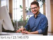 Portrait of happy businessman working on computer at creative office. Стоковое фото, агентство Wavebreak Media / Фотобанк Лори