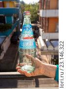 Купить «Бутылка из-под минеральной воды Pejo в руке на фоне городской улицы», фото № 23146322, снято 6 ноября 2013 г. (c) Евгений Ткачёв / Фотобанк Лори