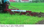 Купить «Молодой тракторист пашет на тракторе в дождь», видеоролик № 23155810, снято 24 июня 2016 г. (c) Сергей Буторин / Фотобанк Лори