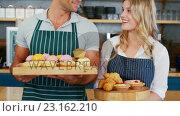 Купить «Waiter and waitress showing plates with snacks», видеоролик № 23162210, снято 22 июля 2018 г. (c) Wavebreak Media / Фотобанк Лори