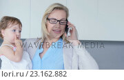 Купить «Mother making a call while holding her baby», видеоролик № 23162882, снято 10 апреля 2020 г. (c) Wavebreak Media / Фотобанк Лори