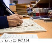 Купить «Библиотекарь заполняет формуляр читателя», эксклюзивное фото № 23167134, снято 22 марта 2016 г. (c) Вячеслав Палес / Фотобанк Лори