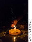 Купить «Горящая свеча и рука со спичкой на столе в темноте», фото № 23169594, снято 10 июня 2016 г. (c) Василий Кочетков / Фотобанк Лори