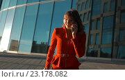 Купить «Деловая женщина в красном отвечает на звонок», видеоролик № 23178082, снято 27 июня 2016 г. (c) Алексей Собченко / Фотобанк Лори