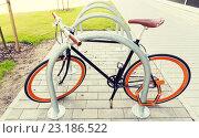 Купить «close up of bicycle locked at street parking», фото № 23186522, снято 30 мая 2015 г. (c) Syda Productions / Фотобанк Лори
