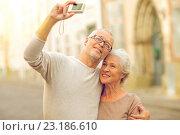 Купить «senior couple photographing on city street», фото № 23186610, снято 4 сентября 2014 г. (c) Syda Productions / Фотобанк Лори