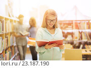 Купить «happy student girl or woman with book in library», фото № 23187190, снято 6 марта 2015 г. (c) Syda Productions / Фотобанк Лори