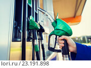 Купить «close up of hand holding hose at gas station», фото № 23191898, снято 5 ноября 2015 г. (c) Syda Productions / Фотобанк Лори