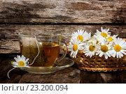 Купить «Ромашковый чай. Лекарственный настой в прозрачной чашке и ромашки», фото № 23200094, снято 3 июля 2016 г. (c) Наталья Осипова / Фотобанк Лори