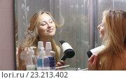 Купить «smiling girl drying her hair», видеоролик № 23213402, снято 14 мая 2016 г. (c) Яков Филимонов / Фотобанк Лори