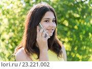Купить «Cute girl talking on phone in park», фото № 23221002, снято 2 июля 2016 г. (c) Володина Ольга / Фотобанк Лори