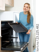 Купить «Woman placing roasting tray in kitchen oven», фото № 23225482, снято 20 сентября 2018 г. (c) Яков Филимонов / Фотобанк Лори