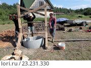Купить «Рабочие опускают кольца в новый колодец», фото № 23231330, снято 3 июля 2016 г. (c) Elizaveta Kharicheva / Фотобанк Лори