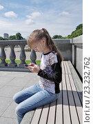 Купить «Девочка с сотовым телефоном сидит на скамейке в парке», эксклюзивное фото № 23232762, снято 9 июля 2016 г. (c) Илюхина Наталья / Фотобанк Лори
