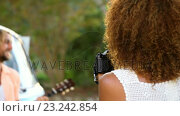 Купить «Woman taking a picture of a man playing guitar», видеоролик № 23242854, снято 14 декабря 2018 г. (c) Wavebreak Media / Фотобанк Лори