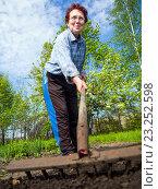 Купить «Пожилая женщина разравнивает землю с помощью граблей», эксклюзивное фото № 23252598, снято 5 мая 2016 г. (c) Вячеслав Палес / Фотобанк Лори