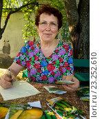 Купить «Пожилая женщина записывает в тетрадь данные по высаженным семенам», эксклюзивное фото № 23252610, снято 5 мая 2016 г. (c) Вячеслав Палес / Фотобанк Лори