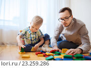 Купить «father and son playing with toy blocks at home», фото № 23259286, снято 19 марта 2016 г. (c) Syda Productions / Фотобанк Лори