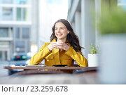 Купить «happy woman drinking cocoa at city street cafe», фото № 23259678, снято 12 мая 2016 г. (c) Syda Productions / Фотобанк Лори