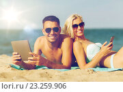 Купить «happy couple with tablet pc sunbathing on beach», фото № 23259906, снято 11 августа 2015 г. (c) Syda Productions / Фотобанк Лори