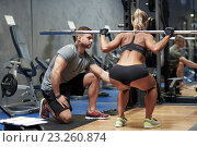 Купить «man and woman with barbell flexing muscles in gym», фото № 23260874, снято 19 апреля 2015 г. (c) Syda Productions / Фотобанк Лори
