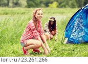 Купить «smiling friends setting up tent outdoors», фото № 23261266, снято 25 июля 2015 г. (c) Syda Productions / Фотобанк Лори