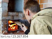 Молодой мужчина разжигает печь на даче. Стоковое фото, фотограф Юлия Михайлова / Фотобанк Лори