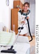 Купить «Happy adult girl vacuuming floor», фото № 23277174, снято 17 августа 2018 г. (c) Яков Филимонов / Фотобанк Лори